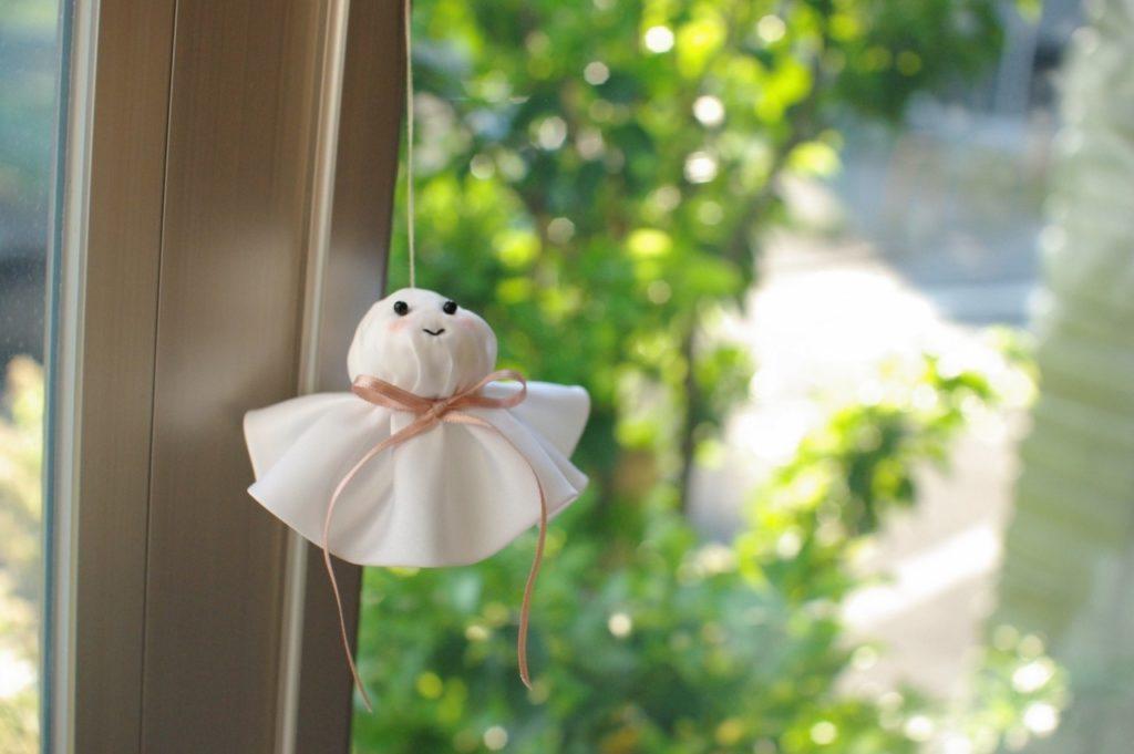 窓辺に飾ってある、てるてる坊主の写真