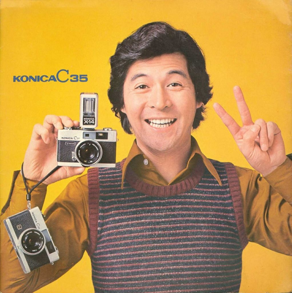 タレントの井上順さんのカメラを持ってピースする写真