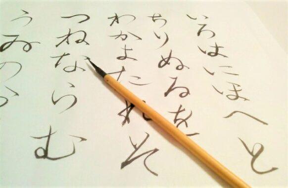 いろは歌の字と筆の写真