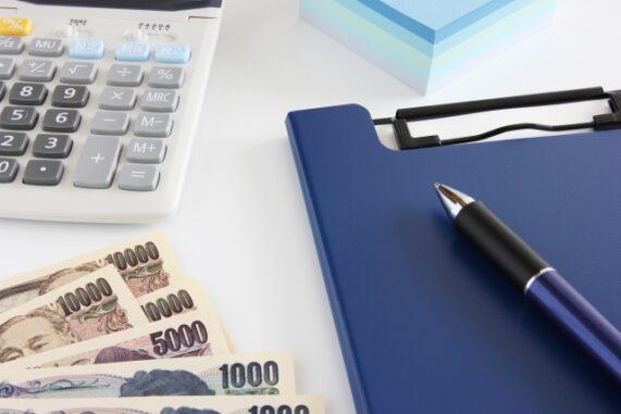 電卓とお金とファイルの写真