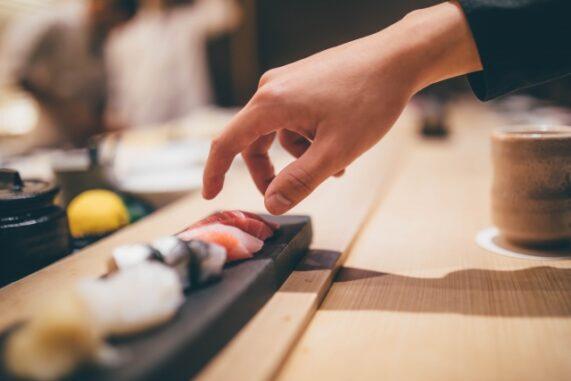 寿司を手でとる人の写真