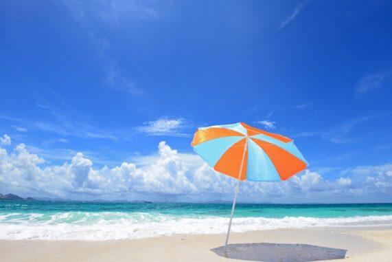 夏の浜辺とビーチパラソルの写真