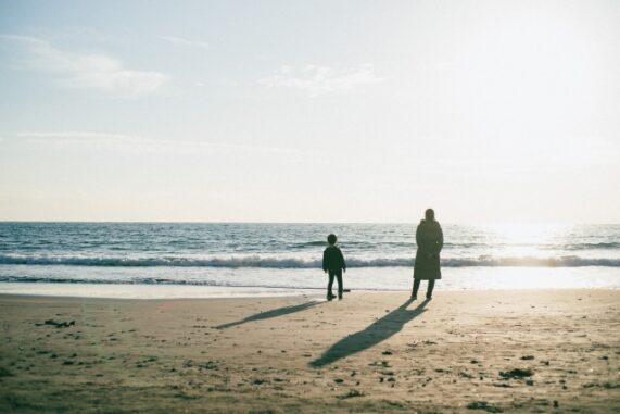 冬の海に佇む親子の写真